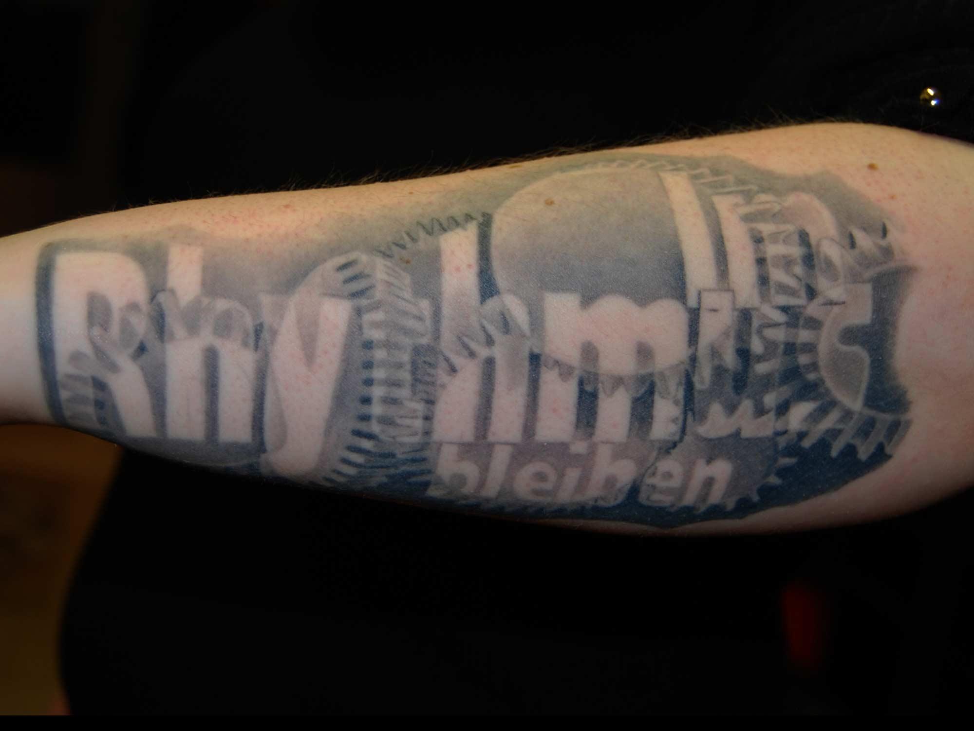 """Zahnräder Tattoo mit Schrift """" im Rhythmus bleiben """" Biomechanik München"""